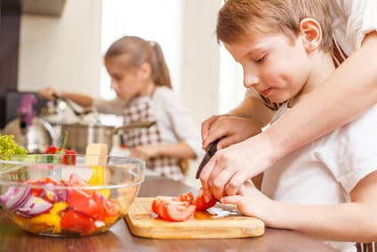 Small boy cutting in sliceKleiner Junge, der mit seiner Mutter in einer modernen Küche Tomaten für einen Salat schneidet.